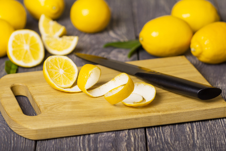 Whole lemons and pieces of fruit with peel on wooden Board next to knife