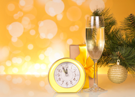 Christmas pine branch with toy, glass of champagne, gift and clock on yellow background