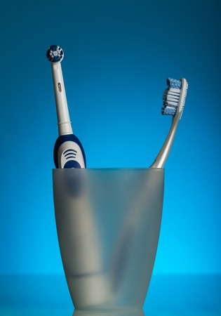 Two toothbrushes in the glass, electric and manual, on blue