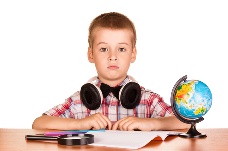 School supplies and boy with headphones engaged at the table, isolated on white