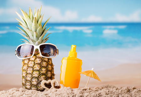 Pineapple with sunglasses, umbrella and sunscreen, on beach