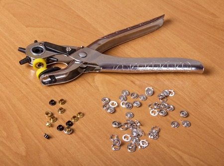 Tool for making holes and installing buttons on clothes, on table