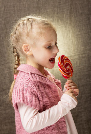 Attractive blond girl eating candy on stick, on gray