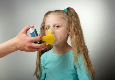 Sick child inhales medicine through mask on gray
