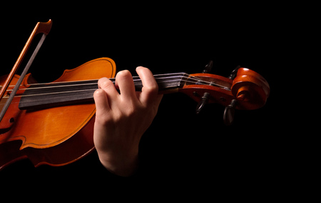 Violin in hands of musician isolated on black