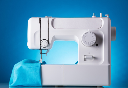 Sewing machine in work with fabric, on blue