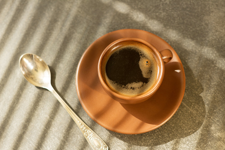 Cup of freshly brewed morning coffee, next to teaspoon, on table
