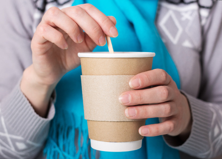 Special Cup for hot coffee takeaway, in hands of woman 스톡 콘텐츠