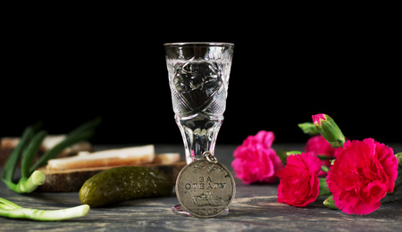 Medal of valor, red carnations and glass of vodka, isolated on black background