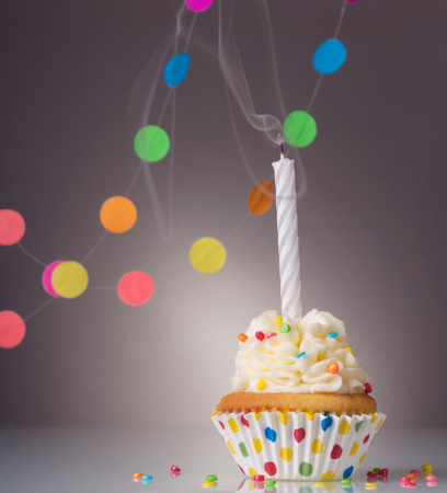Festive birthday cupcake with a candle on a bright background Imagens