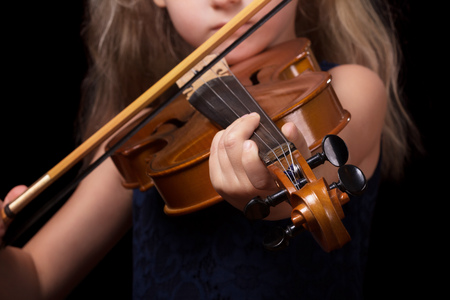 Little blonde girl playing the violin isolated on a black background Banque d'images