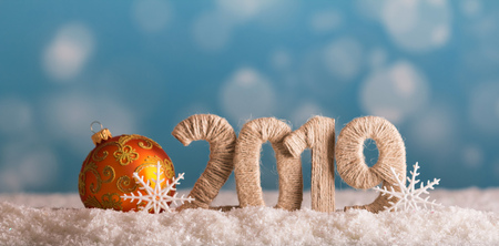 New year inscription 2019 with a snow background and bright yellow christmas ball 스톡 콘텐츠