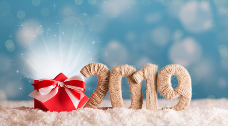 Inscription 2019 new year and red box of magic in the snow on background with bokeh effect 스톡 콘텐츠