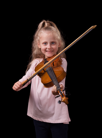 Little blonde girl playing the violin isolated on a black background Stok Fotoğraf