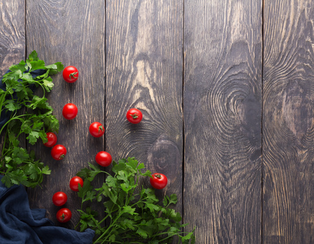 Top view. Juicy little cherry tomatoes and fresh parsley on a wooden boards