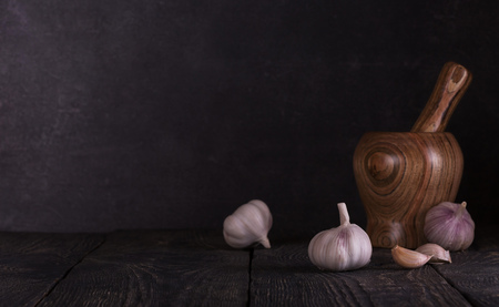 Composition in low key from the mortar for grinding spices and fresh heads of garlic on dark boards