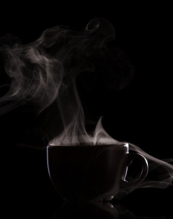 Silhouette of a cup with a hot drink and steam isolated on black background