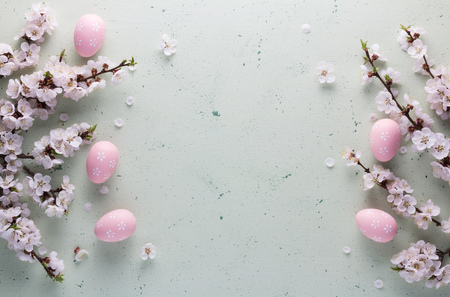 Easter composition in the high key of the flowering branches of apricot and pink Easter eggs