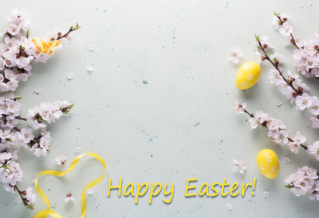 Easter card. Flowering branches of apricot, colorful Easter eggs and a beautiful butterfly on a light background 版權商用圖片