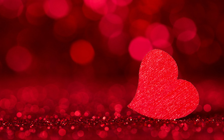 Holiday card. Bright red heart on a red background with bokeh effect