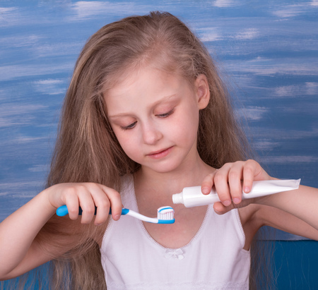 Nice little girl takes care of his teeth, squeezing toothpaste on a toothbrush