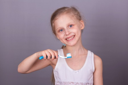 Smiling little girl with tooth paste and brush on gray background