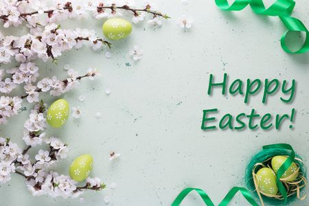 Inscription happy Easter on a light background decorated with bright green ribbon with flowers and easter eggs 版權商用圖片