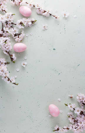 Happy Easter, flowering branches and the eggs painted in a delicate pink color on a light background