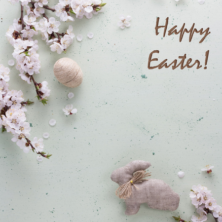 Easter Bunny is handmade from burlap, decorative balls of twine and flowers on a light background