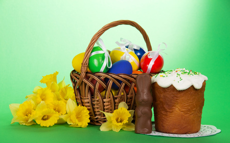 Basket with eggs, an easter cake, a chocolate rabbit and a bouquet of narcissuses on a green background