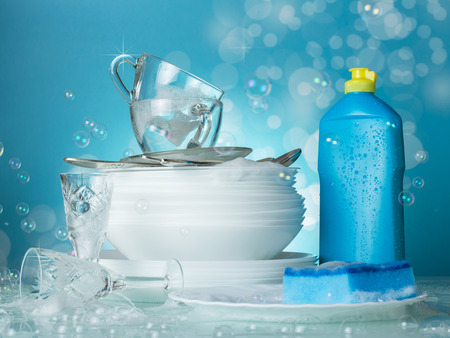 Clean washed dishes, dishwashing and soap bubbles on blue background Stock Photo