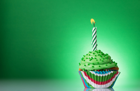 Vanilla cupcake with butter cream with a burning candle on a green background