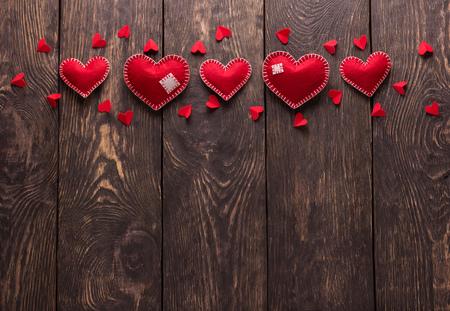 Bright red felt heart handmade on dark wooden boards