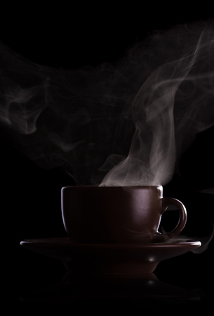 Dark cup of hot coffee and steam, isolated on black background 版權商用圖片