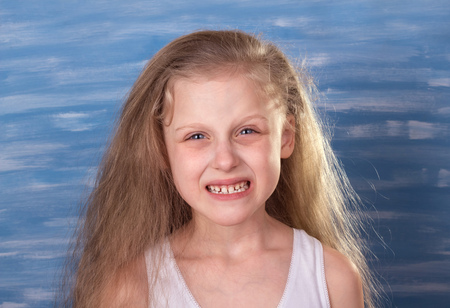 The little blonde girl shows her milk teeth on a light background