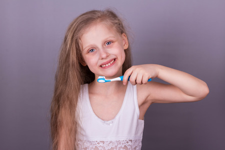Concept of caring for the teeth. Little smiling girl brushing her teeth over grey background