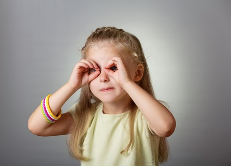 Little cute girl looking through binoculars from his fingers on gray background