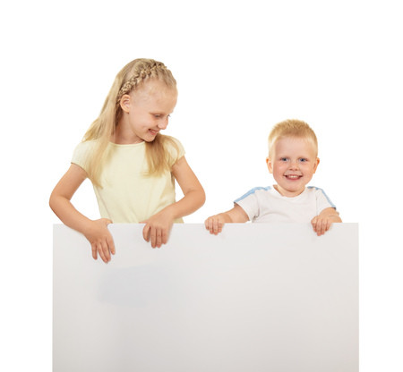 Little boy and girl smiling and holding a blank white banner isolated on white background