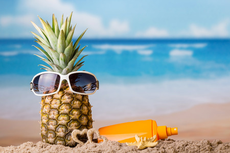 Sun beach. The concept of rest. Pineapple in sunglasses in sand and cream for sun protection 版權商用圖片