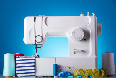 Modern white electric sewing machine with accessories for needlework on a blue background 版權商用圖片
