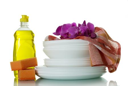 Stack washed dishes, dishwashing detergent, and towel isolated on white background