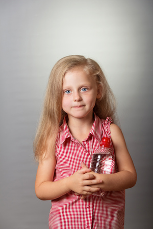 Smiling little girl with piercing eyes and a bottle of water on gray background