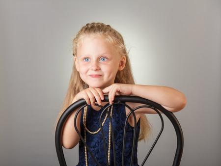 Beautiful little girl dressed in a dark dress and jewelry on gray background 版權商用圖片