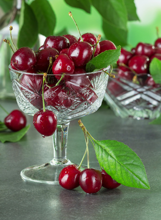 Fresh juicy berries cherries in a crystal vase on the table in the water droplets