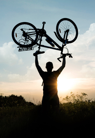 Concept of an active lifestyle. Cycling. Silhouette of a cyclist with a raised up bike up to the sky