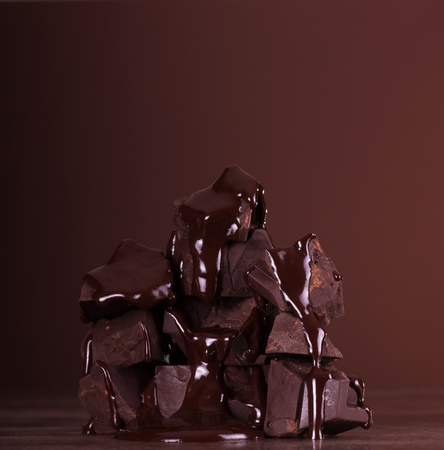 Delicious dark chocolate pieces folded into the tower and a molten chocolate on a brown background