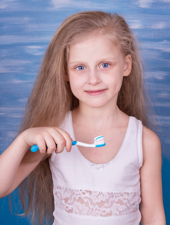 Smiling little girl in white t-shirt with toothbrush and toothpaste on a blue background 版權商用圖片