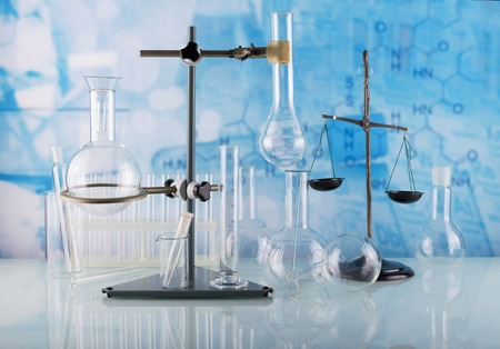 Laboratory conditions. Chemical scales, tripod with laboratory flasks and test tubes on blue background 版權商用圖片