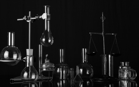 Chemical laboratory a variety of laboratory flasks and test tubes, chemical scales and the burner. Black-and-white photograph