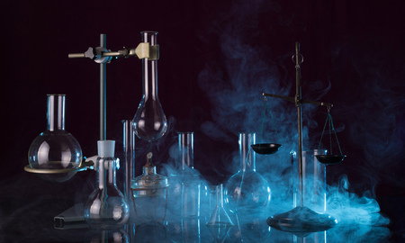 Laboratory glassware, chemical scales, tripod and a torch on a dark background in the smoke 版權商用圖片 - 124679745
